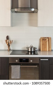 The pan is on a ceramic cooking plate in the new modern kitchen with extractor hood and oven