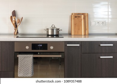 The pan is on a ceramic stove. Light kitchen with oven, cutting board and other elements of kitchen utensils