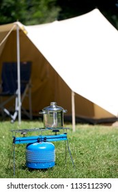 Pan on gas burner with tent in the background