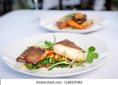 Pan roasted sable fish with spring vegetables on a white plate in a restaurant