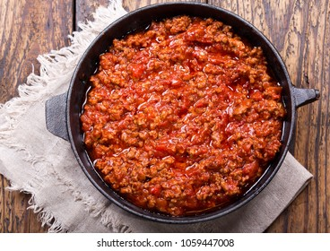 pan of sauce bolognese on wooden table, top view