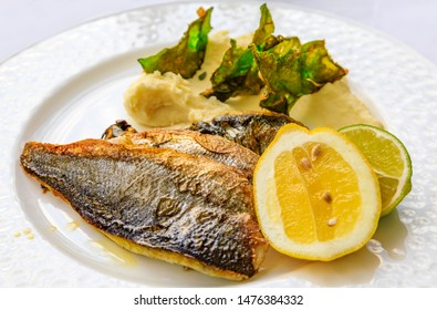Pan seared branzino or sea bass served with lemon and lime wedges, and mashed potatoes with fried kale chips at an al fresco restaurant in Montenegro