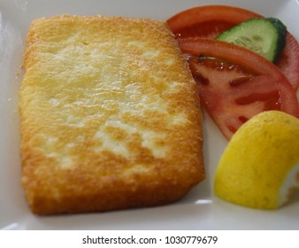 Pan seared Saganaki cheese: a traditional greek meze dish served  with lemon  and fresh vegetables, a delicious appetizer