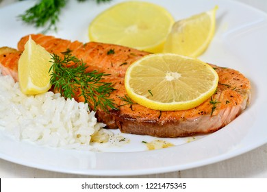 Pan seared salmon fillet steak with rice, lemon, garlic and dill on white plate, shallow dof.