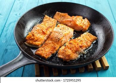 Pan seared salmon fillets on cast iron skillet