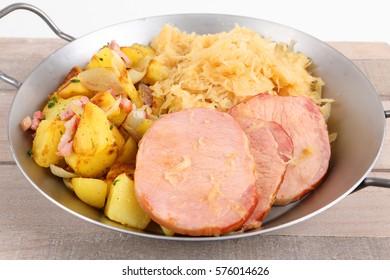 A pan with smoked pork chop an potatoes