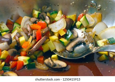 A pan and spoon full of juicy, delicious freshly sauteed organic vegetables