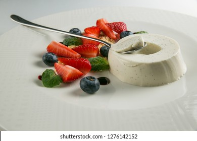 Pana cotta with strawberries & bluberries isolated _ closeup_ light backgtound