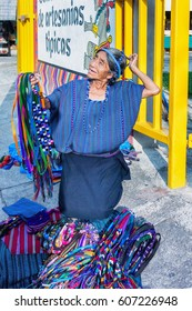 Panajachel, Guatemala - December 8, 2016: Local woman selling on main street in the busy town of Panajachel. Vendors sell traditional textiles. The town is a popular gateway to the lake Atitlan.