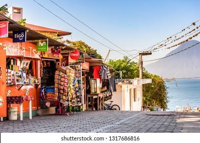 Panajachel, Lake Atitlan, Guatemala - December 29, 2018: Local stores above jetty for public boats headed to lakeside villages in Panajachel with San Pedro volcano behind on Lake Atitlan.