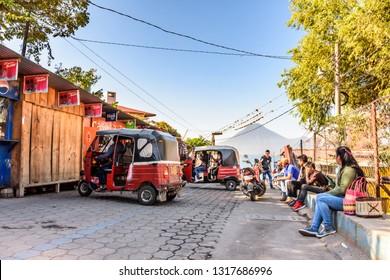 Panajachel, Lake Atitlan, Guatemala - December 29, 2018: Locals & tuk tuks wait above jetty for public boats headed to lakeside villages in Panajachel with San Pedro volcano behind on Lake Atitlan.