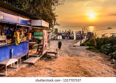 Panajachel, Lake Atitlan, Guatemala - December 29, 2018: Lakeside stores & public ferry boats moored at jetty with faint shadow of San Pedro volcano in haze & golden hour glow behind on Lake Atitlan.