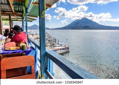Panajachel, Lake Atitlan, Guatemala - December 25, 2018: Lakeside restaurant on Christmas Day in Panajachel with Atitlan & Toliman volcanoes behind on Lake Atitlan.
