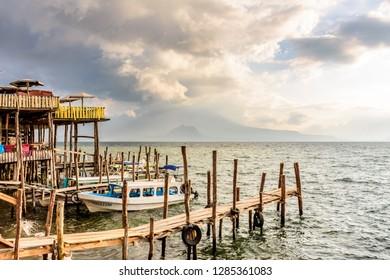 Panajachel, Lake Atitlan, Guatemala - November 12, 2018: Lakeside restaurants, jetties & boats with cloudy view of Toliman & Atitlan volcanoes behind in Panajachel on Lake Atitlan.
