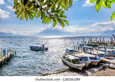Panajachel, Lake Atitlan, Guatemala - November 12, 2018: Boats &  jetties with San Pedro volcano behind in Panajachel on Lake Atitlan in Guatemalan highlands.