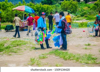 Panajachel, Solola, Guatemala, September 13, 2018, two young people planting among a multitude of people and selling vanes trumpet tapes, sharing the market to sell and earn money for the day of indep