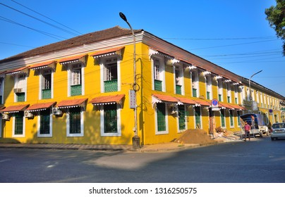 Panaji, India - January 23, 2019: People walking in front of a old, yellow Portuguese house in the street.