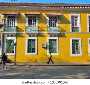 Panaji, India - January 23, 2019: A man walking in front of an old, yellow Portuguese building in the street.