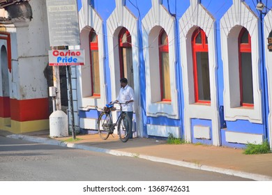 Panaji, India - January 23, 2019: A man standing with a cycle in front of a blue building.