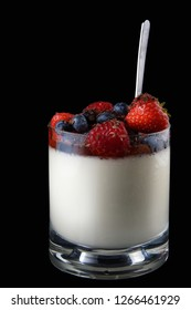 Panakota creamy Italian dessert in a glass cup with berries and a spoon