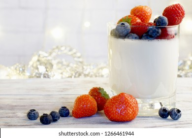 Panakota in a glass beaker with bright berries on a light wooden table