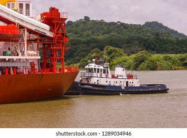 PANAMA - AUGUST 15, 2009: Tugboat pushes ship on the Panama Canal.