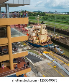 Panama Canal, Panama, Central America - May 31st, 2017:  Ships transporting cargo to world wide destinations give no indication of a slowing global economy.  Tourists watch from observation decks.