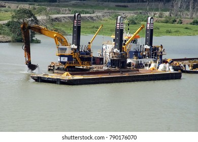 PANAMA CANAL - DEC 16, 2017 - Dredge shovel boat fills barge to keep shipping channel clear in the Panama Canal