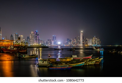 Panama City, Panama - march 2018: Skyline and fisher boats at night. Illuminated cityscape of Panama City  business district view from fisher boat harbour.