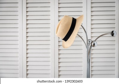 A panama hat hangs on a metal coat rack with a background of doors with white lacquered lamas