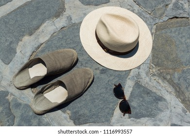 A panama hat, a pair of espadrilles and a pair of sunglasses laying on the brick ground