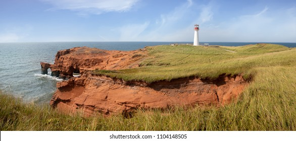 Panarama of the Borgot, or Cape Herisse lighthouse of Cap aux Meules, Magdalen Islands, Canada. The lighthouse stands on the rugged red cliffs of the Etang du Nord.