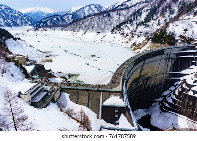 Panarama landscape aerial view of kurobe dam cover with snow and water in reservoir become ice with row of mountain and cloudy blue sky background,Toyama(tateyama alpine route),Japan.