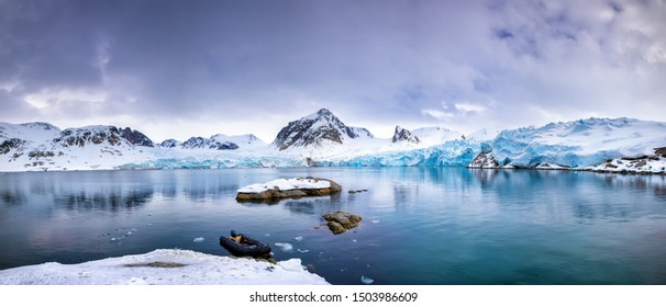 Panarama of the mountains, snow and blue glacial ice of the Smeerenburg glacier, Svalbard, and archipelago between mainland Norway and the North Pole. An inflatable boat is anchored in the foreground,
