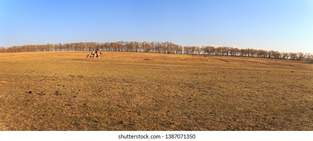 Panarama View of The grassland in early spring, A man riding horse at the grassland in Zhang Bei grassland, Heibei, China