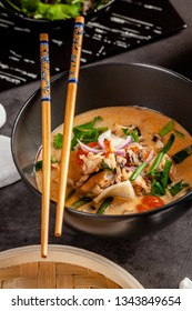Pan-Asian cuisine concept. Japanese miso soup Tom Yam Kung with seafood, shrimps, mussels, calamari. Serving dishes in the restaurant in the bowl. Background image.