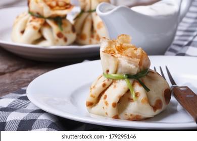 Pancake bag with green onion closeup on a white plate.