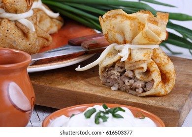 Pancake bags with meat and cheese served with sour cream on a white wooden background