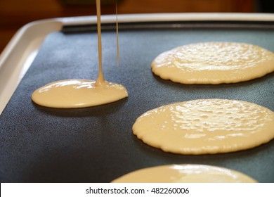 Pancake batter baking mix being poured from a bowl onto a hot electric griddle cooking delicious breakfast meal for a family.
