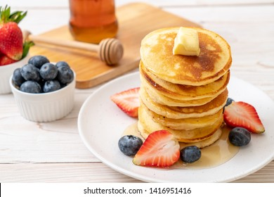 pancake with butter, strawberries, blueberries and honey