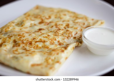 Pancake with cottage cheese on a white plate