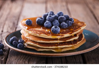 Pancake folded stack of with liquid honey and fresh blueberries on wooden background.selective focus.