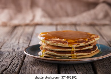 Pancake folded stack of with liquid honey on wooden background.selective focus.