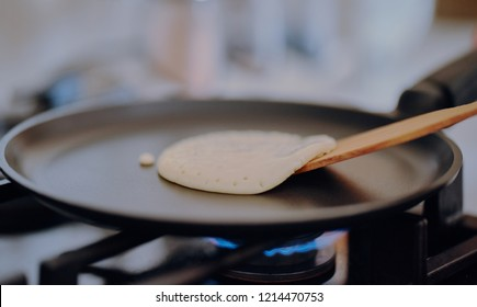 Pancake is fried in a skillet. A girl with a wooden spatula turns the pancake to the other side.