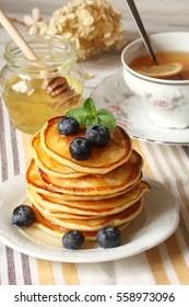 pancake with honey and blueberries on a white plate, mint and grapes