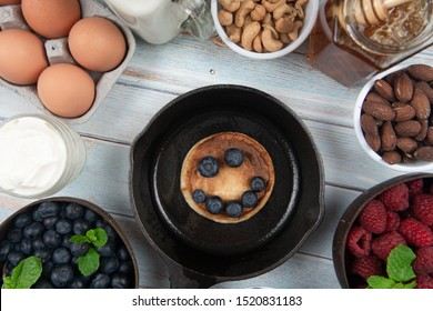 A pancake on an iron cast skillet on rustic wood table with organic eggs, sour cream, honey, milk, raspberry, blueberry, almonds, pecans