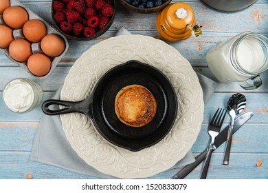 A pancake on an iron cast skillet on rustic wood table with organic eggs, sour cream, honey, milk, raspberries, blueberries