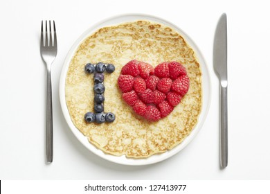 Pancake on plate with love heart shape on white table