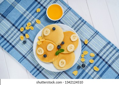 Pancake Plate Blueberry Honey Dessert Top View. Fried Golden Sweet Crepe for Tasty Shrovetide Breakfast. Hotcake Russian Product on Blue Tablecloth with Berry and Banana Chip Morning Flat Lay