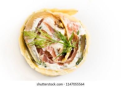pancake roll with smoked salmon, zucchini, cream cheese and herbs on a white plate, top view from above, copy space